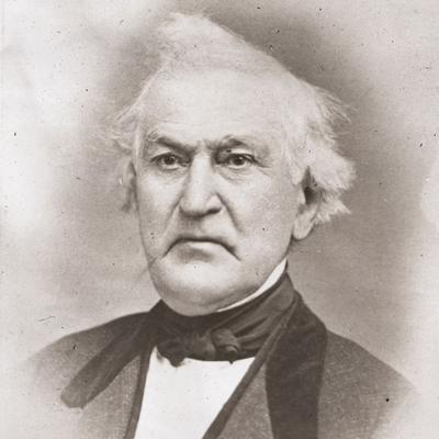 A photograph of David Whitmer. He appears to be frowning a bit. His white hair is somewhat unkempt. He wears a midtone coat, dark vest, dark tie or cravat, and white shirt.