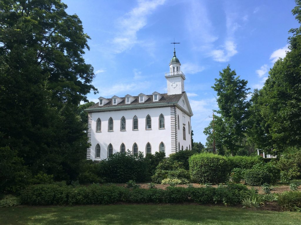 El Templo de Kirtland, un edificio blanco de dos pisos con una torre y un campanario, se ve desde el otro lado de un césped, arbustos y árboles.