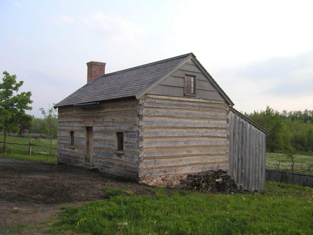 Una casa de troncos de color marrón-grisáceo con una pila de leña al lado.