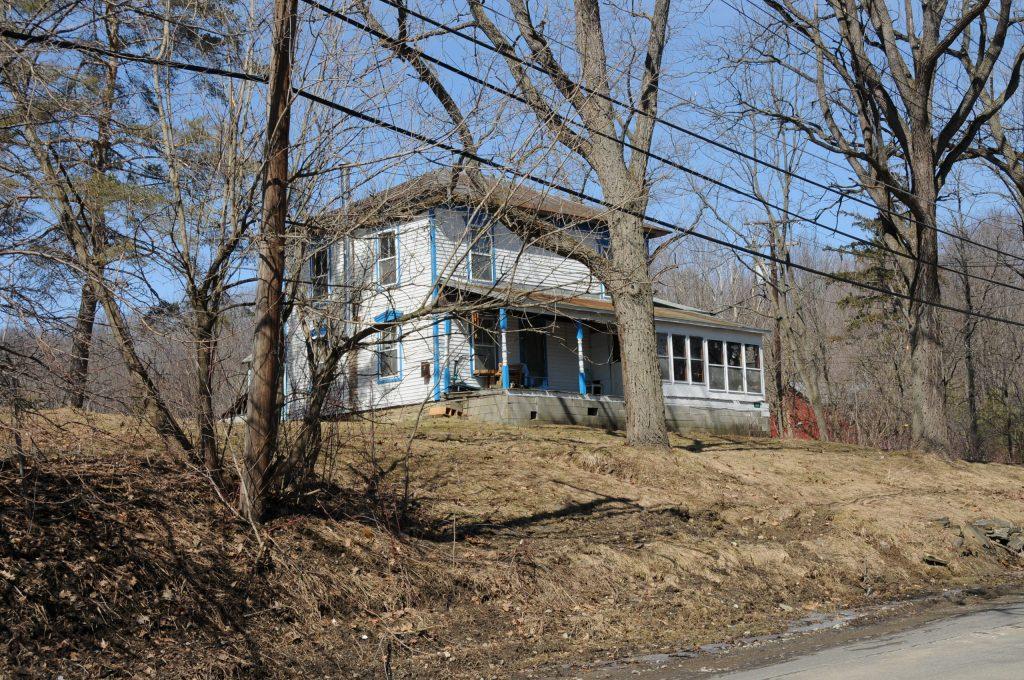 Una casa blanca de dos pisos con detalles azules y un techo marrón se encuentra detrás de los árboles sobre un césped amarillo y marrón.