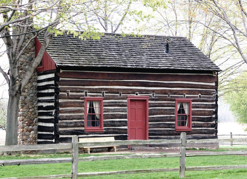 Una casa de troncos marrón con una puerta roja y bordes rojos alrededor de las ventanas se encuentra en el sitio de la casa de los Whitmer
